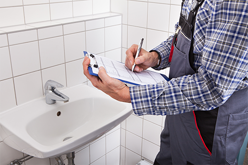 an employee inspecting the washroom equipments with his inspection checklist