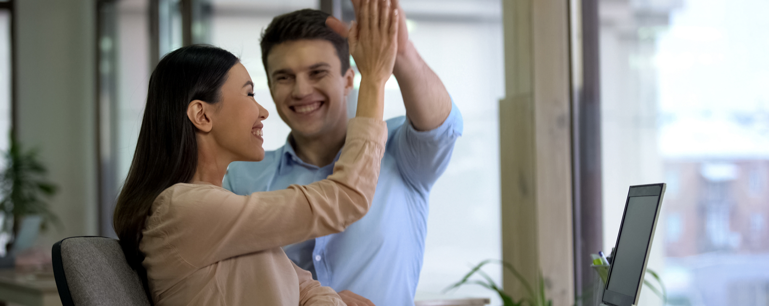 Happy professionals giving high five and smiling