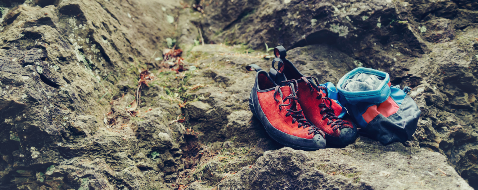 Climbing shoes and chalk bag with magnesium powder on stone rock outdoor fb