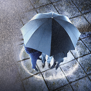 Elevated view of three businesspeople sheltering under one umbrella.png