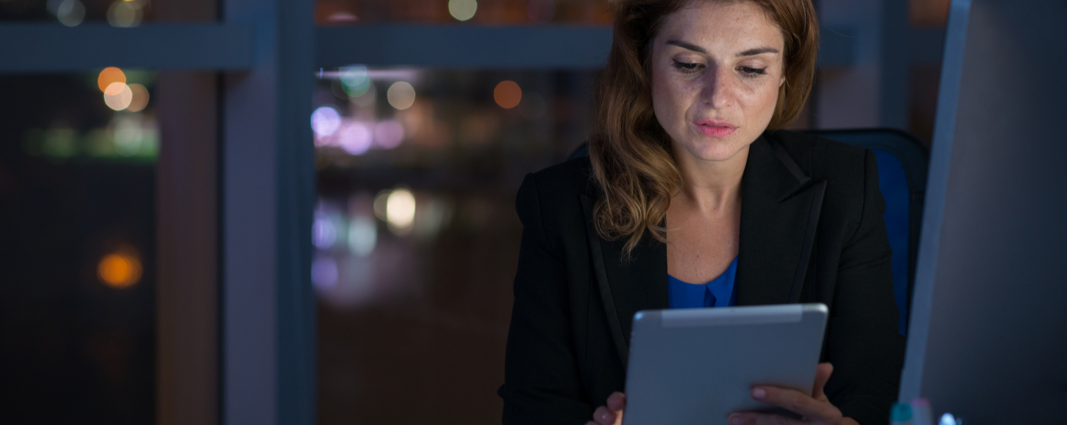 Female professional working on digital tablet in night office