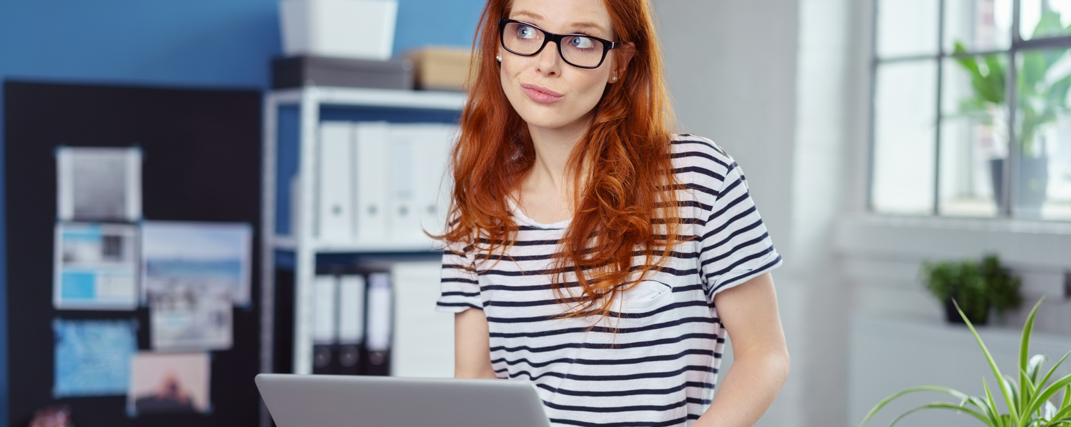 Thoughtful charismatic young redhead woman using a laptop balanced on her lap fb