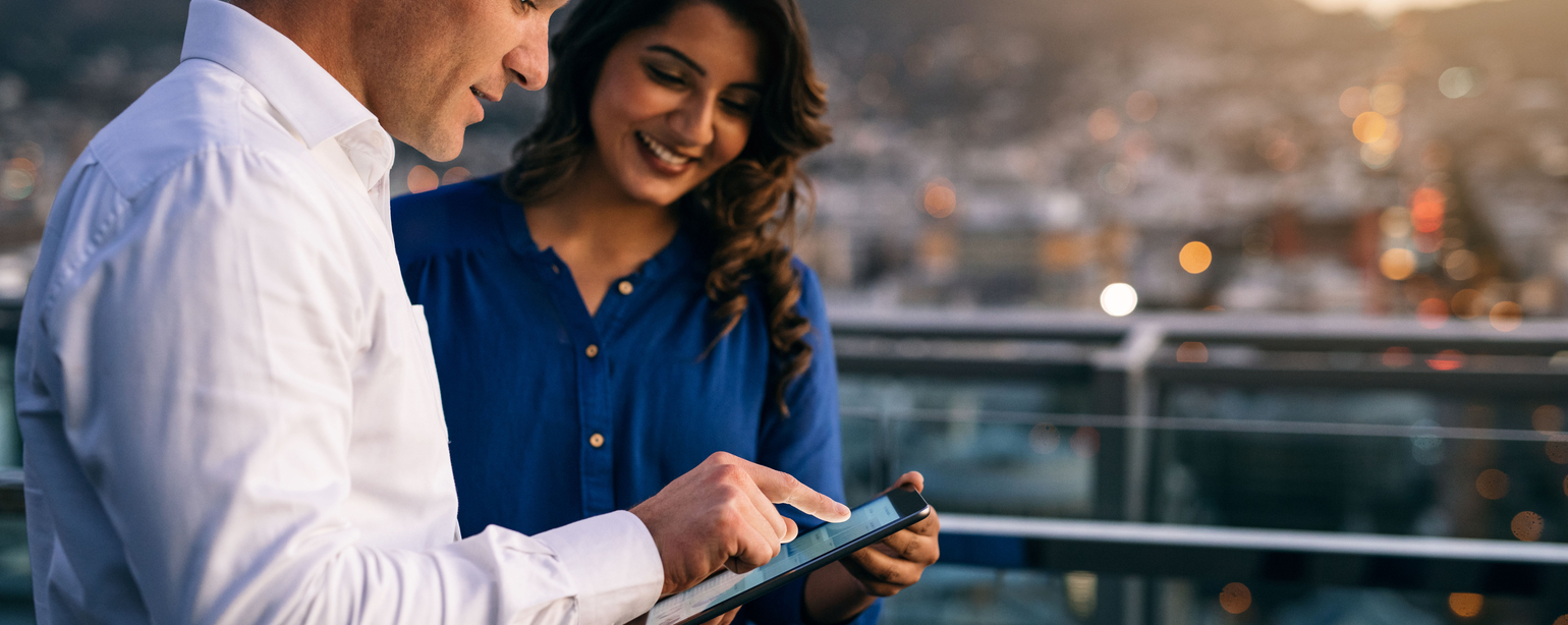 Two smiling coworkers working with a digital tablet together while standing on an office building balcony overlooking the city at dusk