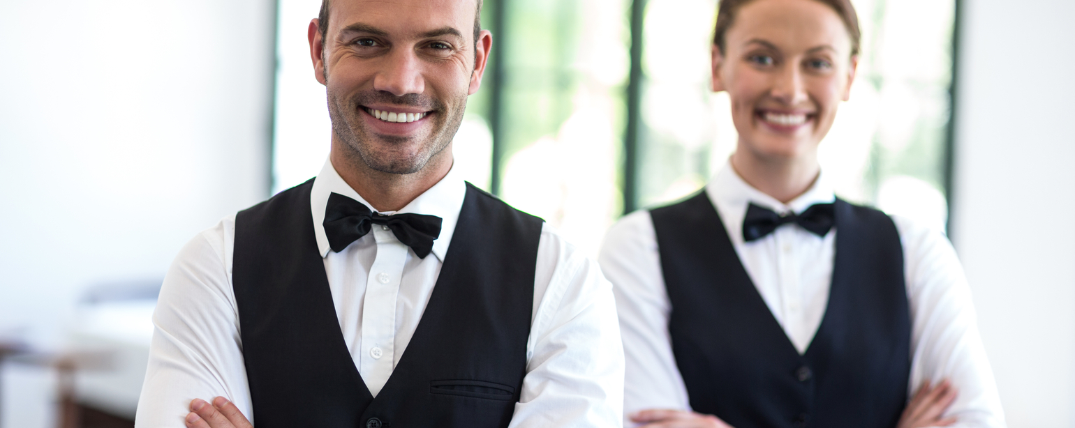 Waiting staff smiling at camera in a commercial kitchen