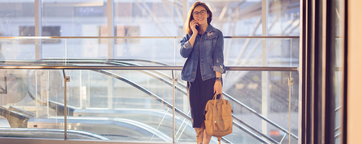 woman talking on mobile phone while holding backpack