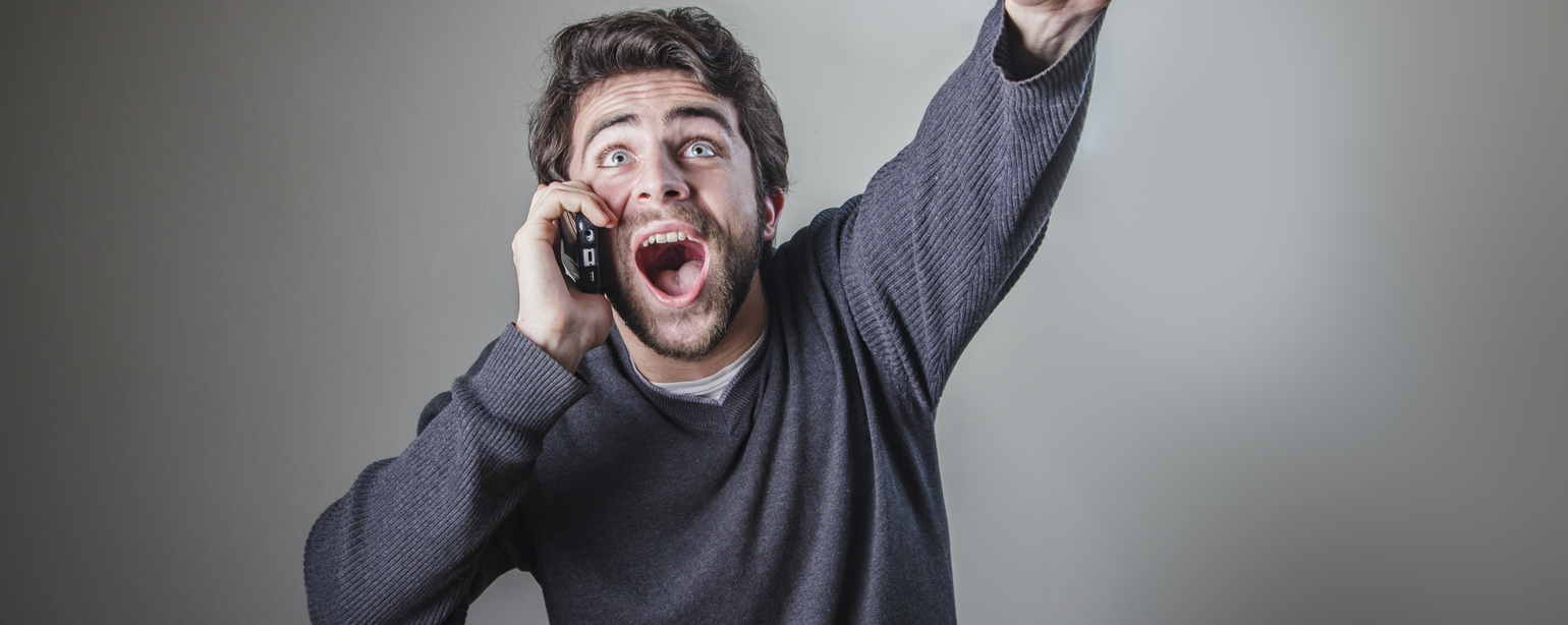 young man receiving great news over his cell phone