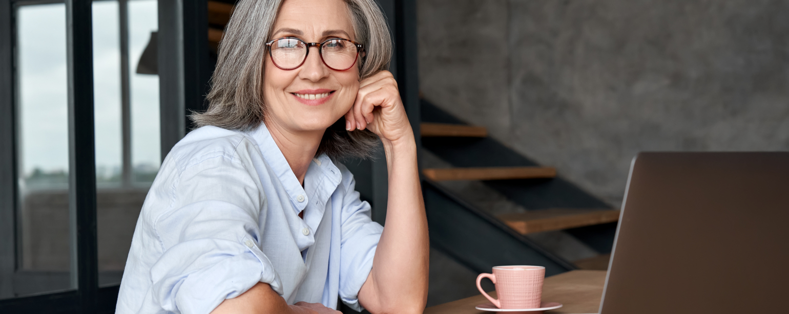 mature gray-haired lady executive looking at camera sitting at table