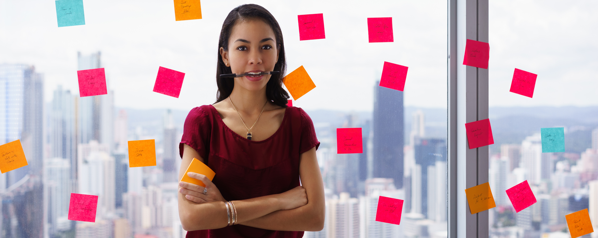 woman stands in office at high floor, against window full of adhesive notes with tasks