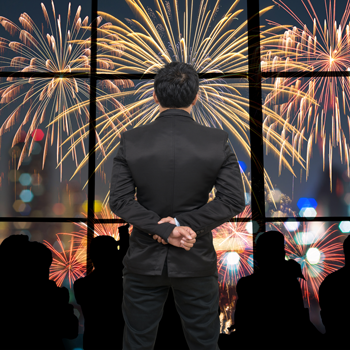 Back-side-of-Businessman-looking-at-fireworks-with-blurred-cityscape-at-night-background