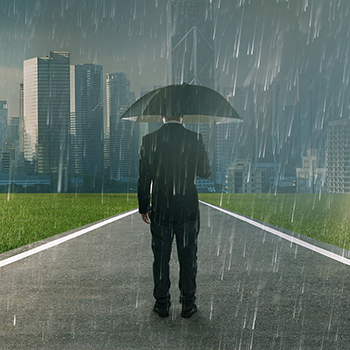 Businessman below storm rain with umbrella
