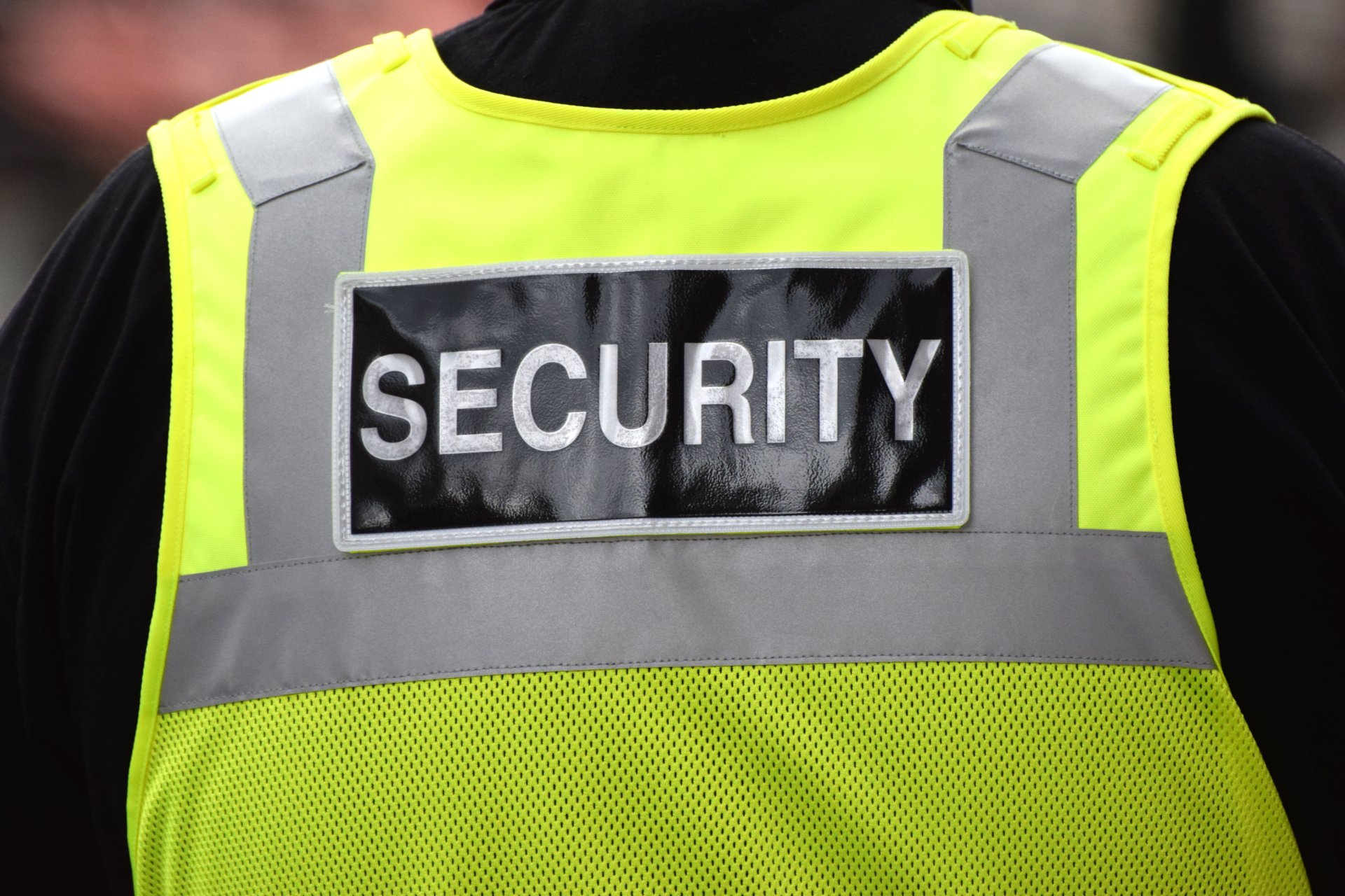 Close up of the word security written on the back of a security guards yellow vest