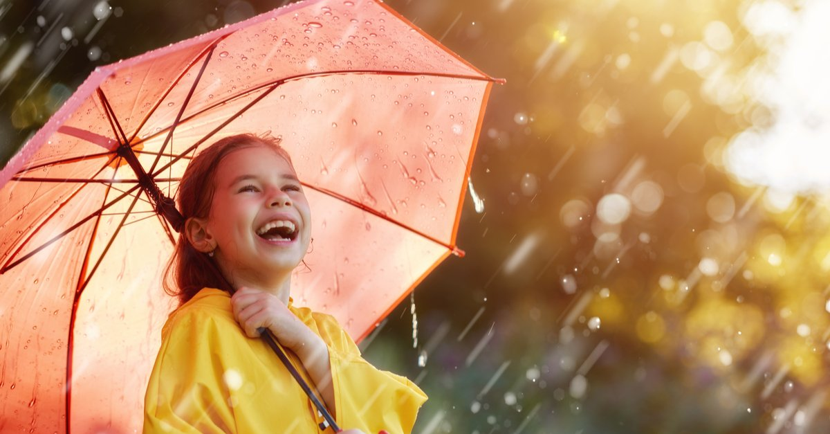 Happy funny child with red umbrella