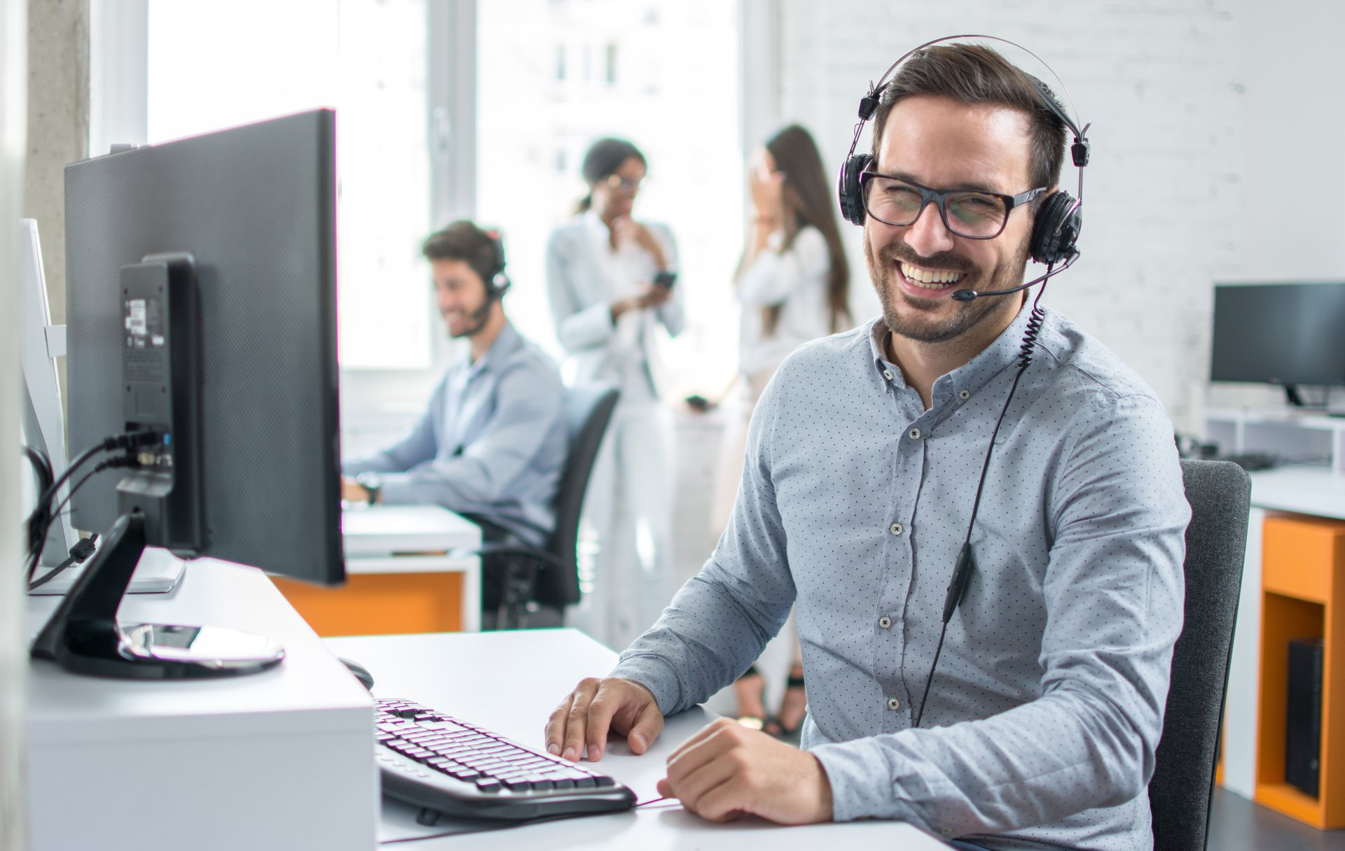 Happy young male customer support executive working in office