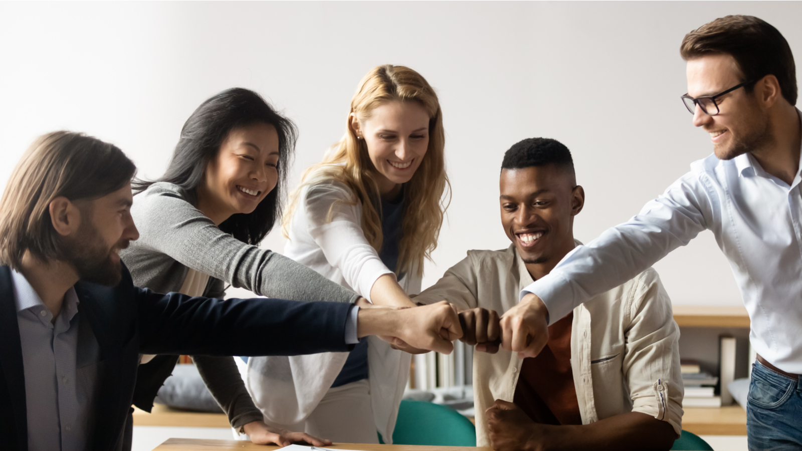 Horizontal image middle-aged and young five multiracial staff members gather in boardroom show unity stacked hands in circle