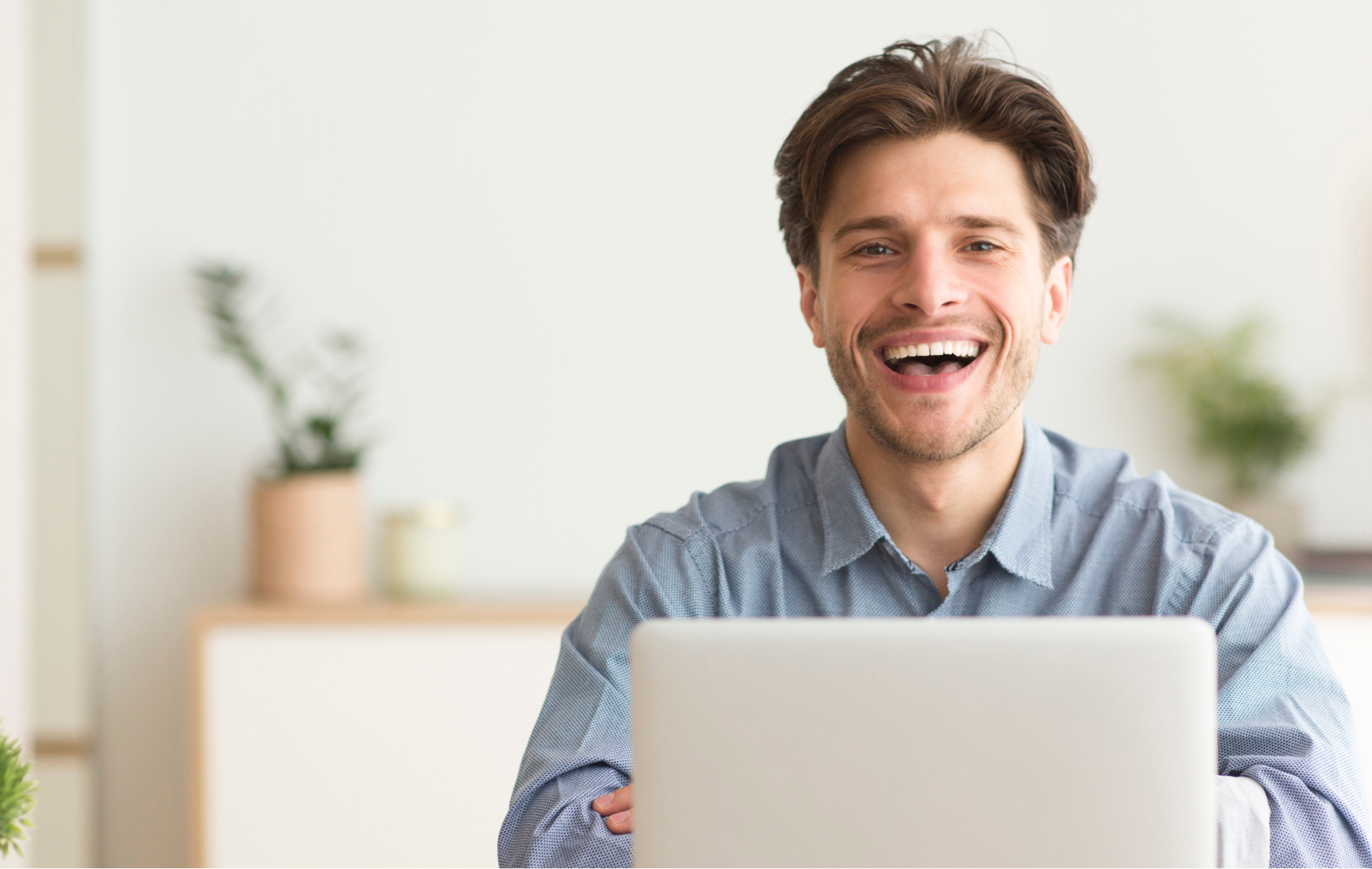 Man Sitting At Laptop And Laughing Looking At Camera Indoor