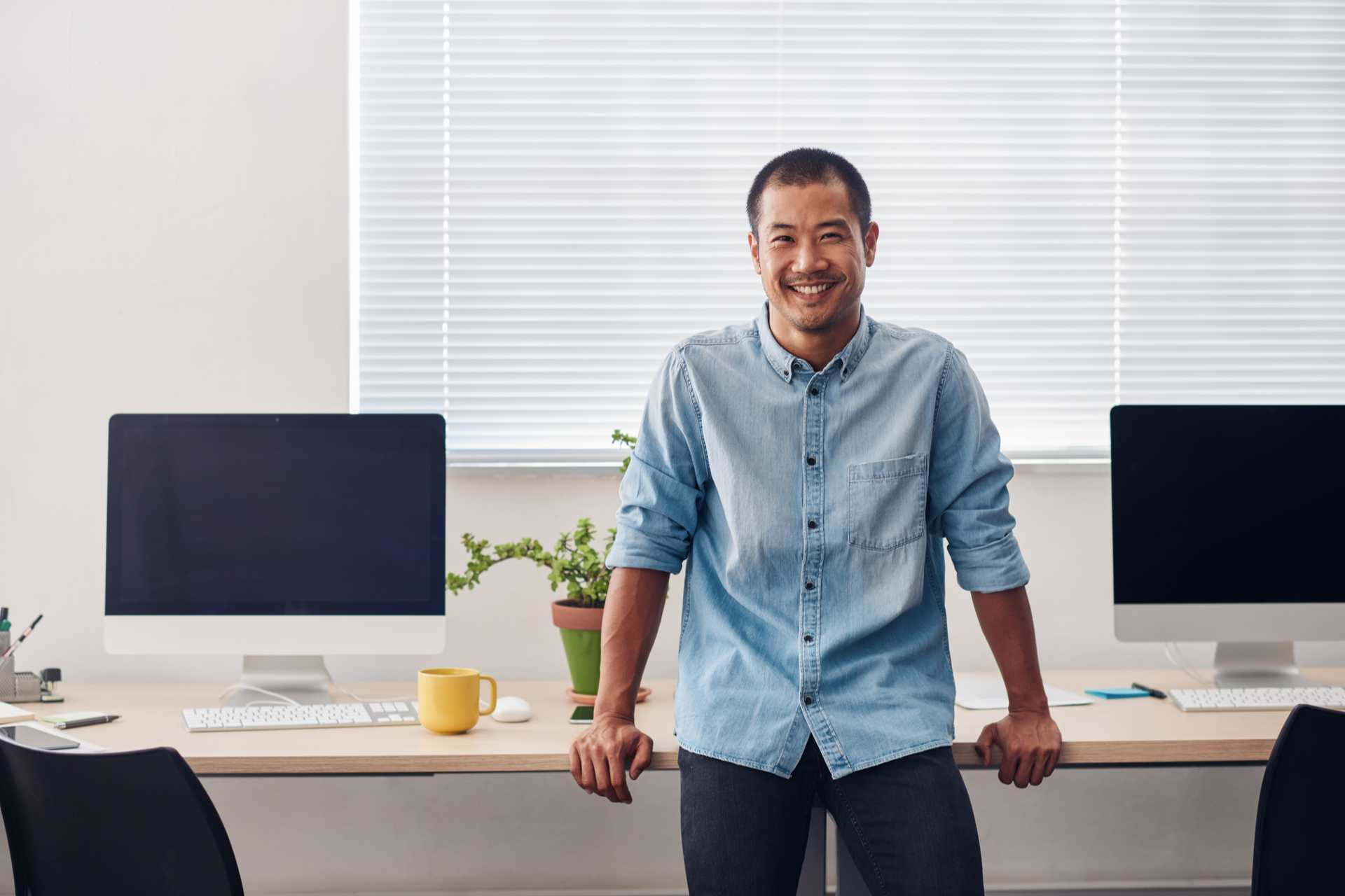 Portrait of a smiling young Asian professional leaning on a computer table