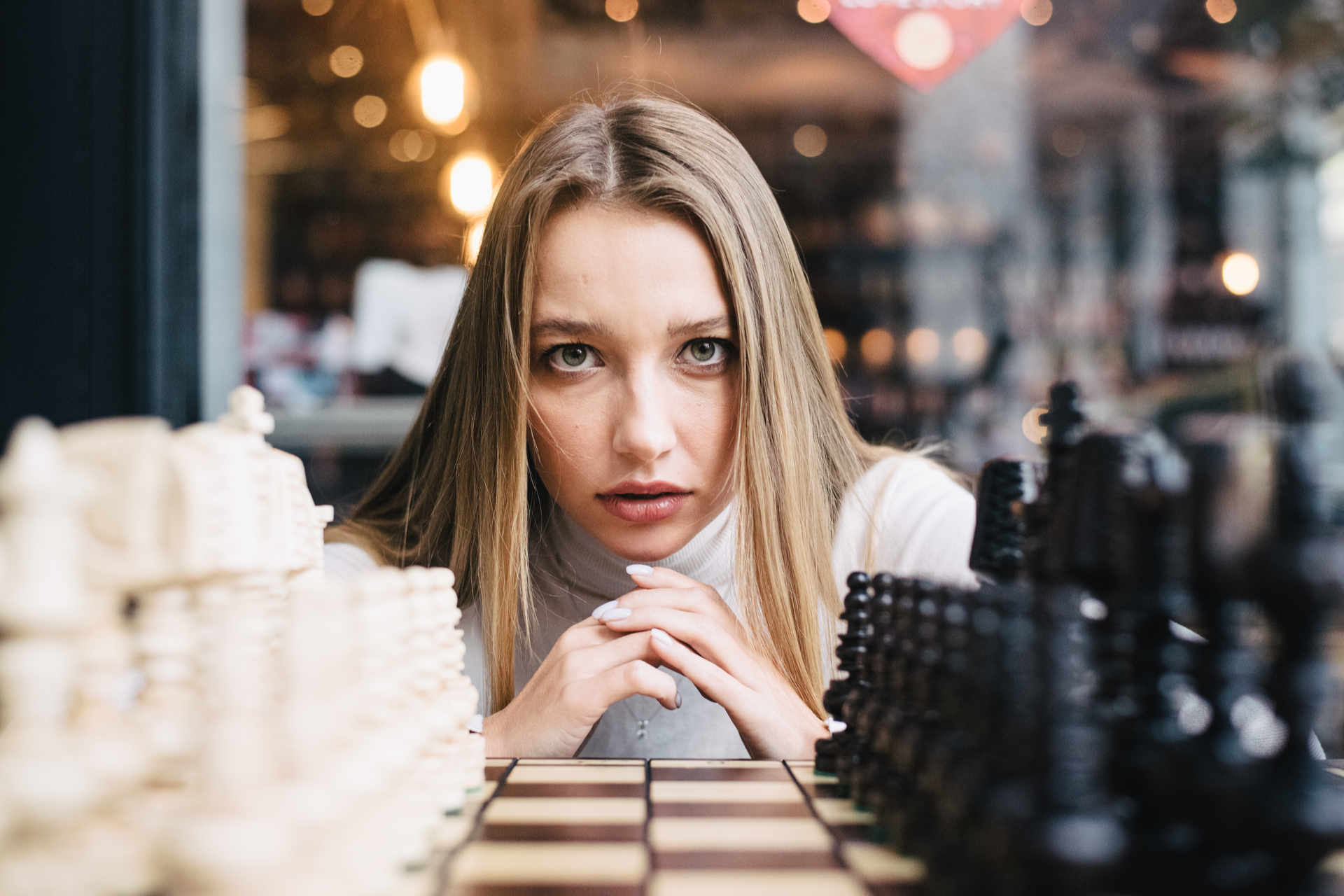 White and black chess pieces are displayed on the board in front of focused woman