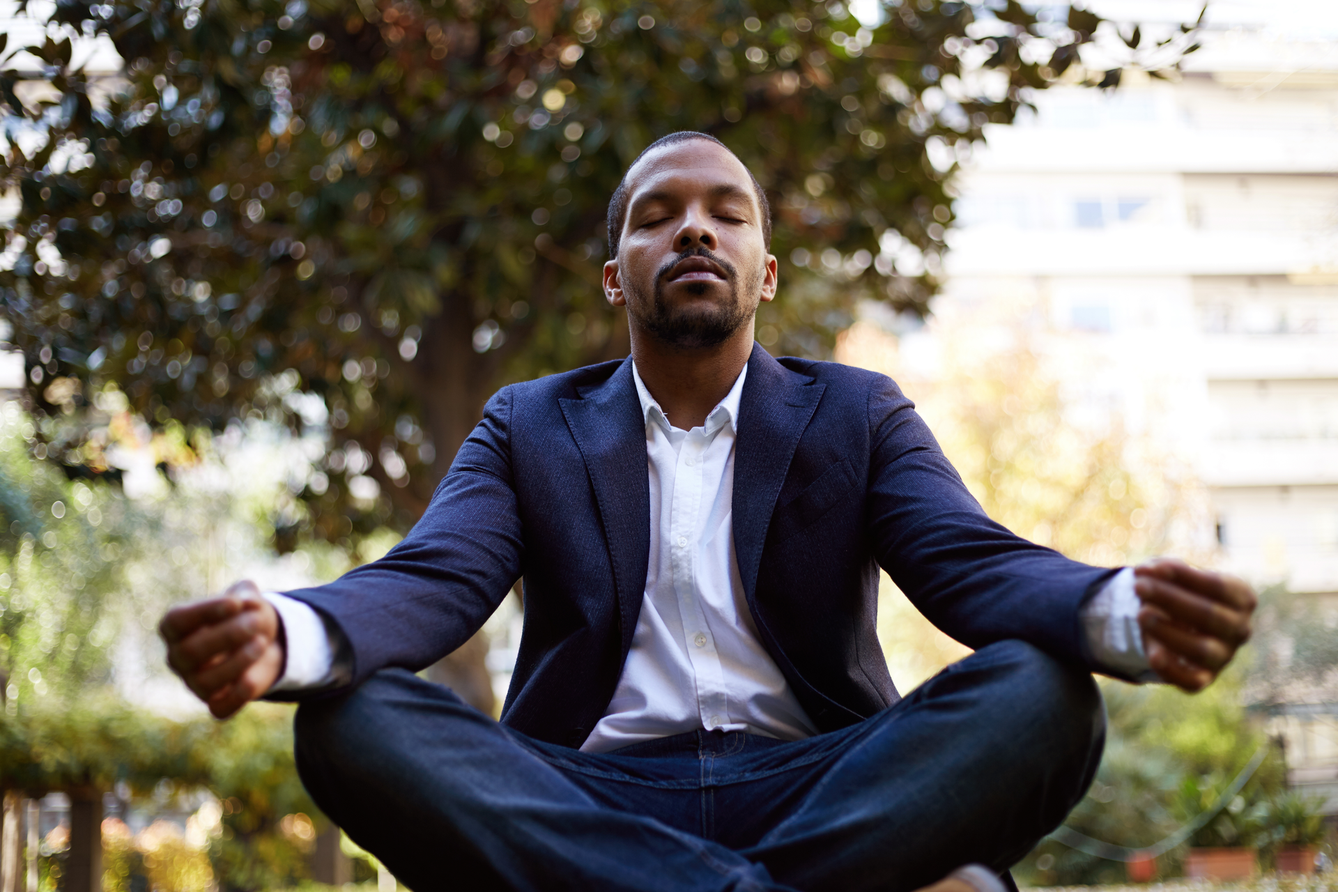 Young male in informal clothes meditating in lotus pose taking a deep breath outside corporate office