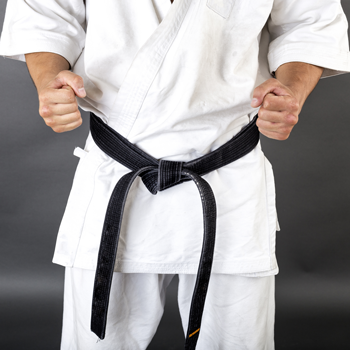 Young-man-in-white-kimono-and-black-belt-training-martial-art-over-gray-background