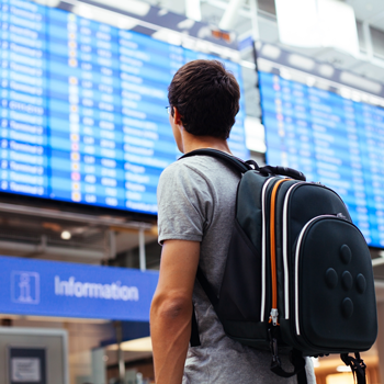 Young-man-with-backpack-in-airport-near-flight-timetable