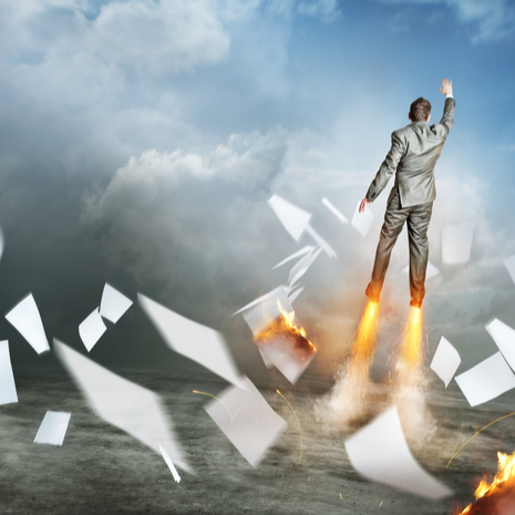 A businessman launching upwards, paperwork flying everywhere!