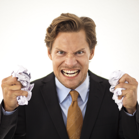 Angry businessman crumbles paper in both hands