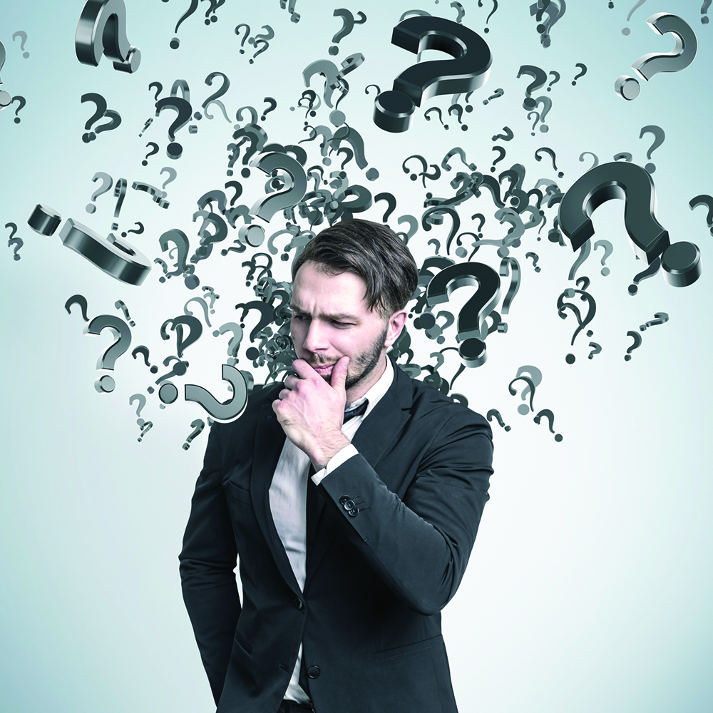 Bearded businessman in a suit is standing near a blue wall with multiple question marks-social.jpg