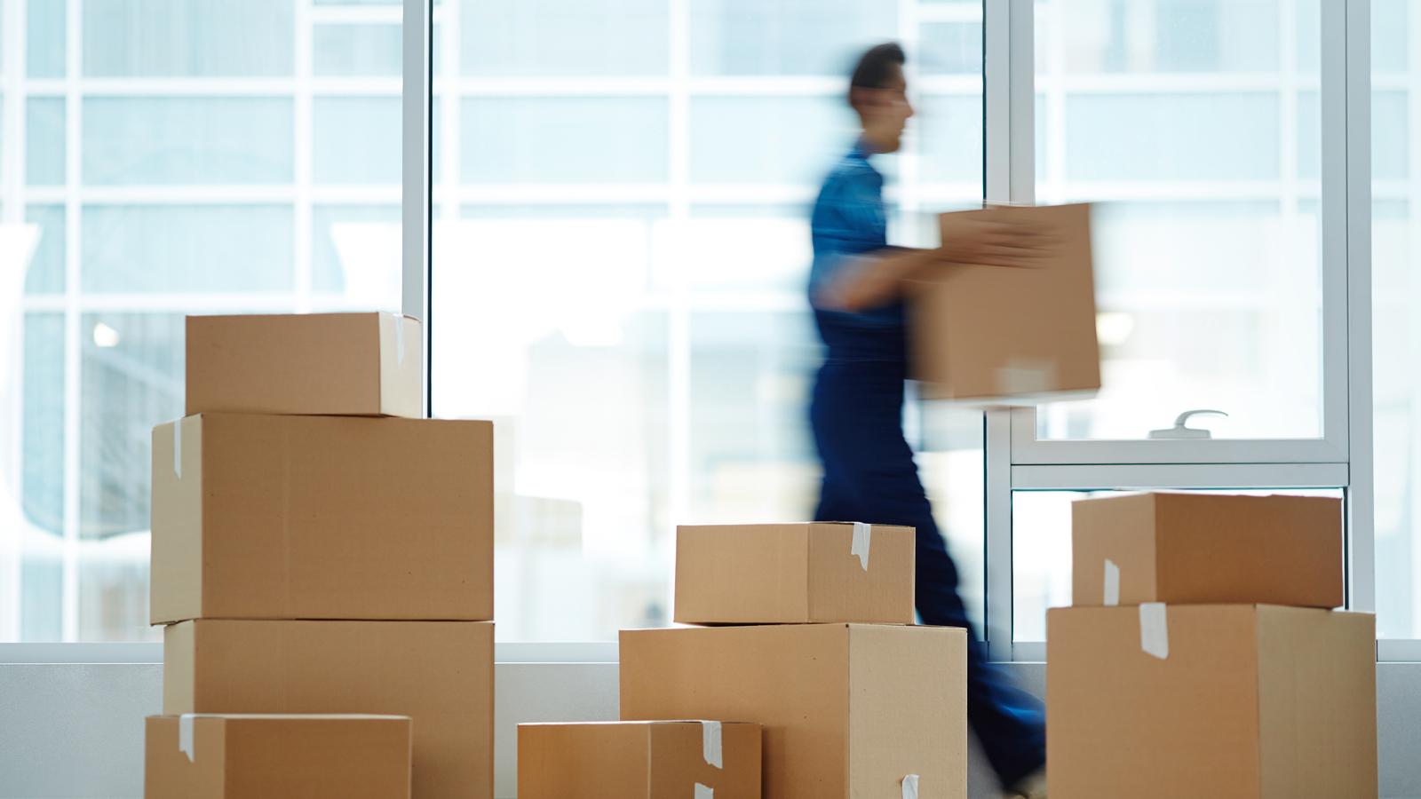 Blurred motion of contemporary worker with packed box walking to new office