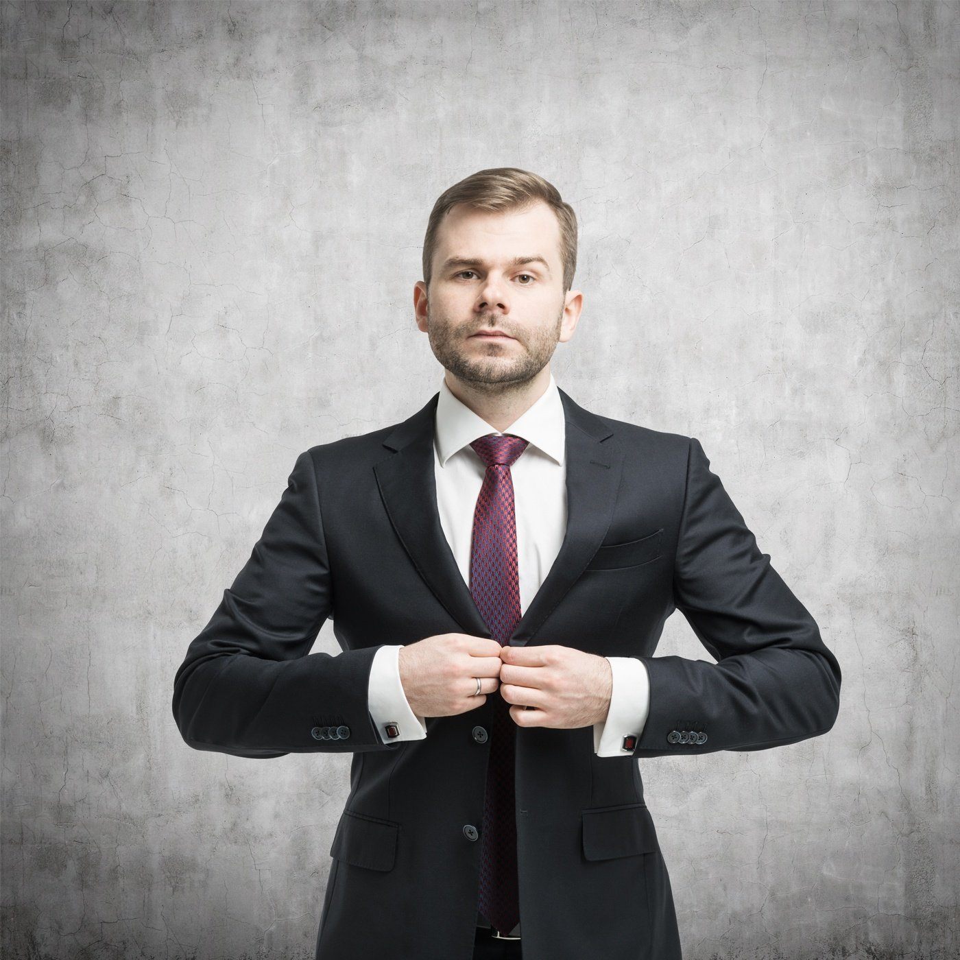 Businessman-standing-in-front-of-the-concrete-wall.jpg