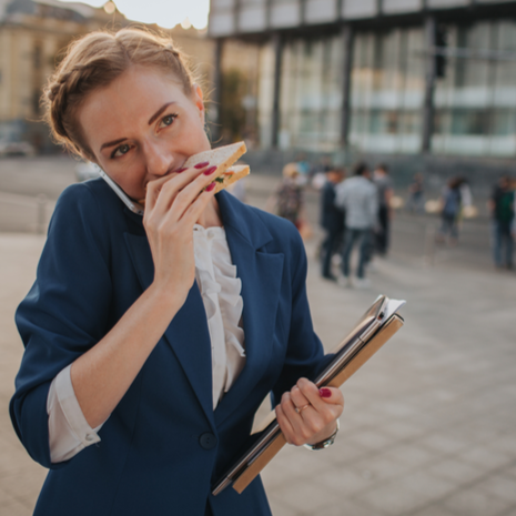 Busy woman in a hurry eating a sandwich and holding folders