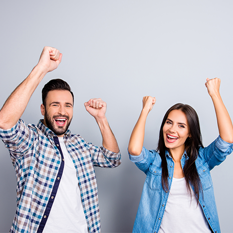 Cheerful couple is celebrating with raised hands