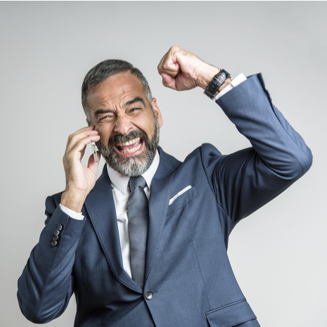 Cheering victorious senior business man receiving great news over his cell phone