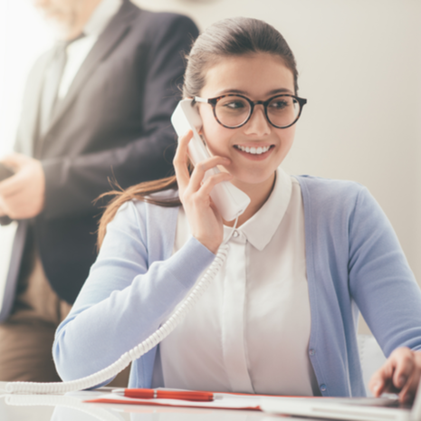 Efficient smiling secretary answering phone calls and talking with customers