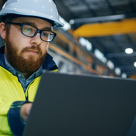Engineer in Hard Hat Wearing Safety Jacket Uses Touchscreen Laptop