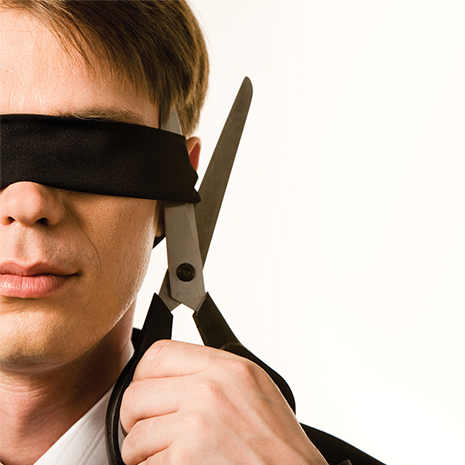 Face of businessman wearing black band on his eyes and holding scissors trying to cut it.png