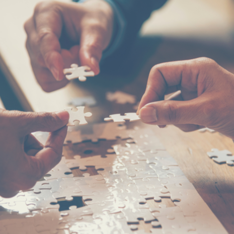 Hands of business people putting puzzle pieces together on table