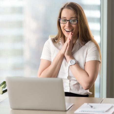 Happy businesswoman laughing with joy at workplace