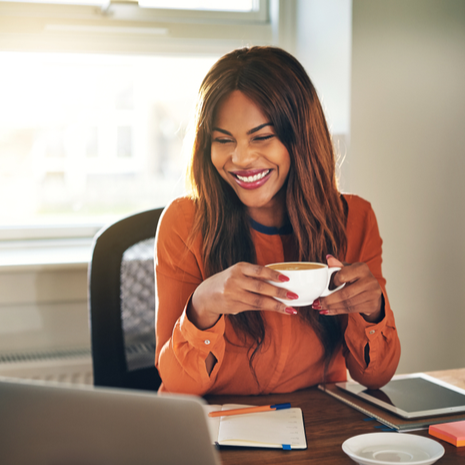 Laughing young female drinking a cup of coffee at office desk