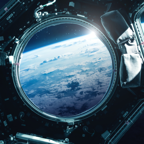 Porthole of space station near the Earth on the background