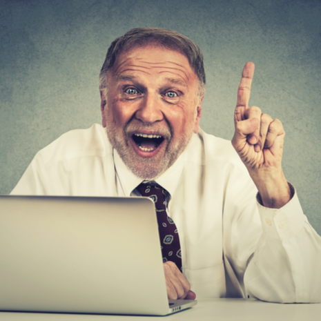 Portrait excited senior man using laptop computer has an idea isolated on gray wall background-1