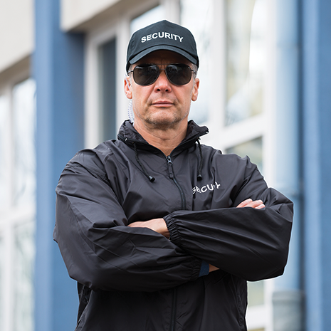 Portrait of confident mature security guard standing arms crossed outside building.png