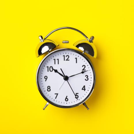 Retro alarm clock on bright yellow background
