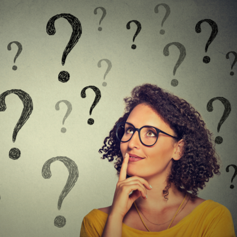 Thinking young business woman in glasses looking up at many question marks isolated on gray wall background