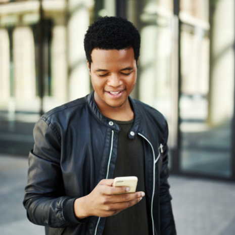 Waist-up portrait of young black man text messaging on his smartphone