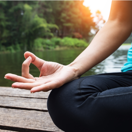Woman exercising yoga at the nature background