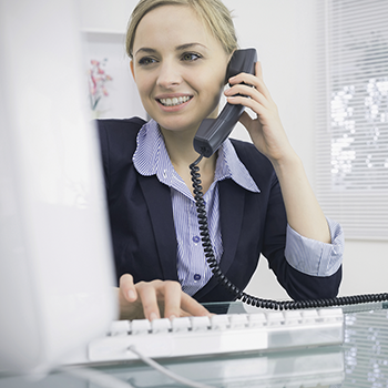 Young female executive using phone and computer at desk in office.png