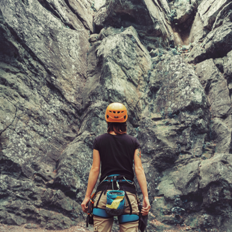 Young woman wearing in climbing equipment standing in front of a stone rock
