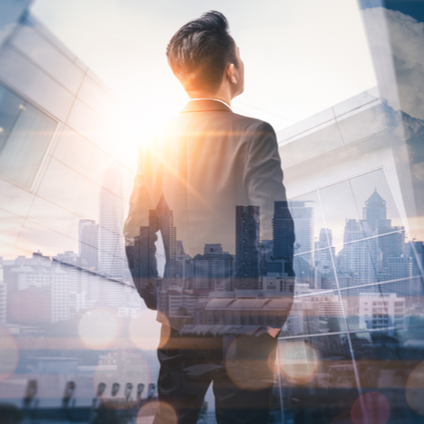 business man standing back during sunrise overlay with cityscape image