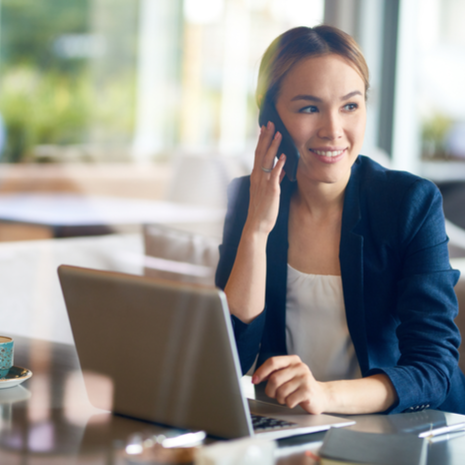 entrepreneur with charming smile talking to her colleague on smartphone