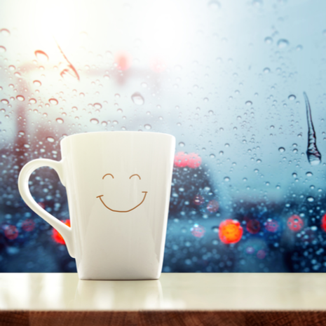 happy Coffee Mug with smiley face on desk inside glass window